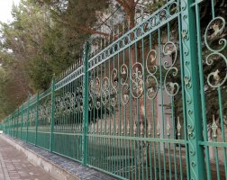 Кованый забор зеленого цвета с патиной