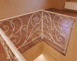 Светлые кованые перила на лестнице в доме